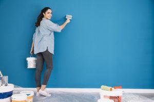 mujer pintando pared azul