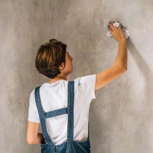 mujer limpiando pared de concreto