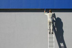 persona pintando pared exterior de azul